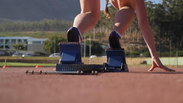CU_Female track athlete accelerating out of start blocks in stadium, at sunrise