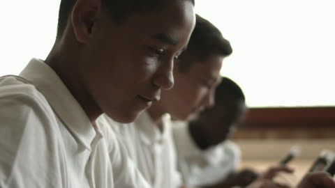 cu_tilt_schoolkids using digital tablets and talking together - adolescence stock videos & royalty-free footage