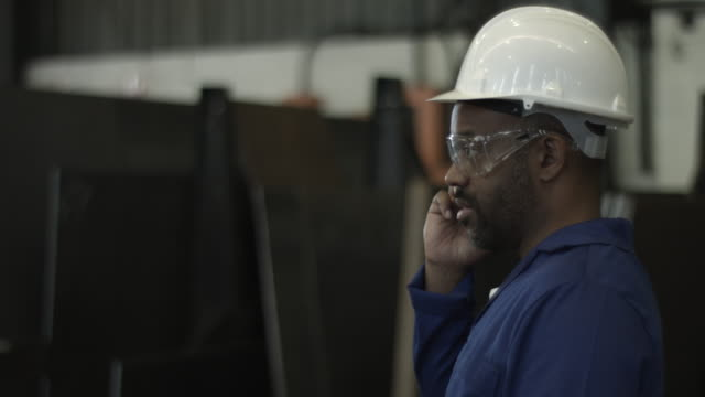 cu_worker at steel plant wearing hard hat, talking on phone - convenience stock videos & royalty-free footage