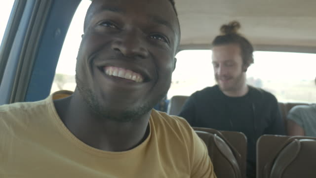 CU_Young guy smiling to camera while riding car with friends