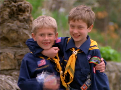 portrait 2 cub scouts hugging + smiling / give thumbs up to camera - cub scout stock videos and b-roll footage