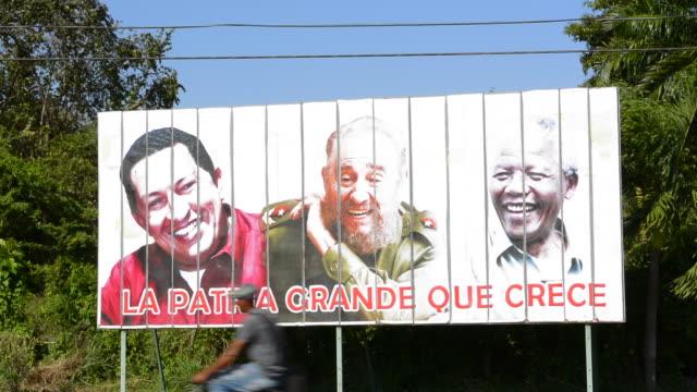 cuba billboard of three heroes in cuban life hugo chavez, fidel castro and nelson mandela near trinidad cuba - ウゴ・チャベス点の映像素材/bロール