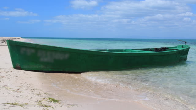 cuba eco tourism in inhabited tropical beach. local fishermen wooden boat in the white sand where gentle waves break. - eco tourism video stock e b–roll