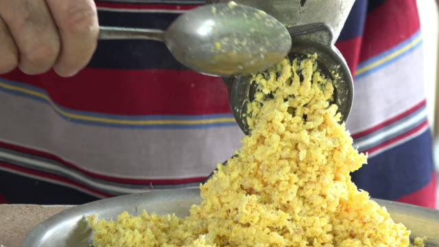 Cuba: Preparing tamales from scratch, grinding corn grains