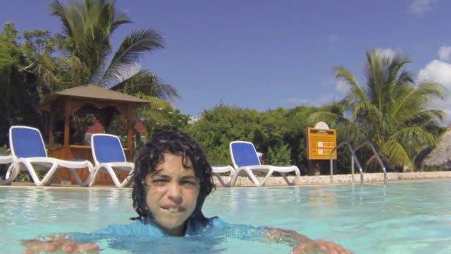 cuba tourism: young boy enjoying swimming pool in resort. the child is in the process of improving his swimming skills. point of view images of tropical climate in the caribbean island - self improvement stock videos & royalty-free footage