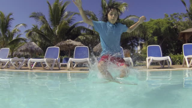 cuba tourism: young boy enjoying swimming pool in resort. the child is in the process of improving his swimming skills. point of view images of tropical climate in the caribbean island - 男児1人点の映像素材/bロール