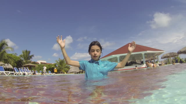 cuba tourism: young boy enjoying swimming pool in resort. the child is in the process of improving his swimming skills. point of view images of tropical climate in the caribbean island - pantaloncino da bagno video stock e b–roll