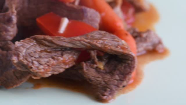 Cuban cuisine: beef stew with red bell peppers. The plate is hot and steaming