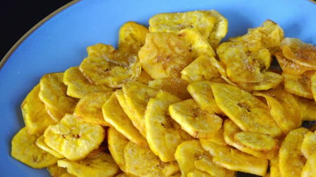 vídeos de stock, filmes e b-roll de cuban cuisine: green plantain chips turning on a display - banana de são tomé