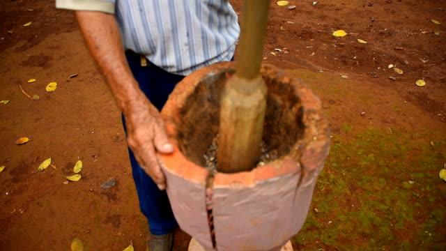 Cuban Farmer Grinding Coffee Grains in Large Wooden Pestle