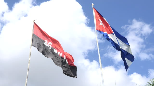 vídeos de stock, filmes e b-roll de cuban flag and the july 26 movement flag flying together in the capiro hill - número 26
