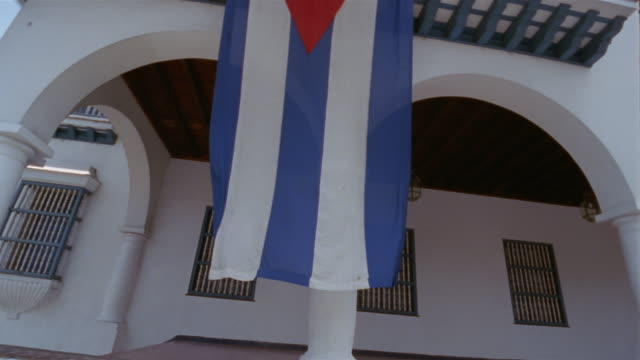 la, cuban flag hanging on spanish colonial style building, santiago de cuba, cuba  - santiago de cuba stock videos and b-roll footage