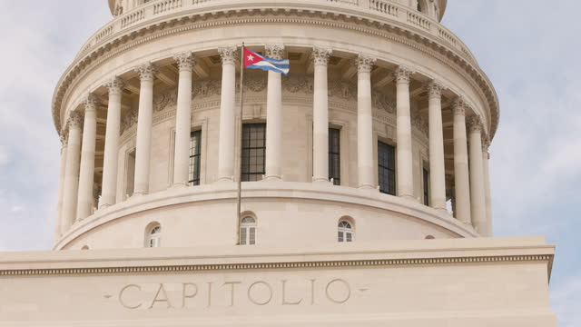 ms cuban flag in front of the capitol state building in havana, cuba - wop productions stock-videos und b-roll-filmmaterial