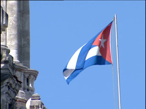 cuban flag on pole against blue sky side of the capital building in edge of shot; havana cuba. - cuba stock videos and b-roll footage