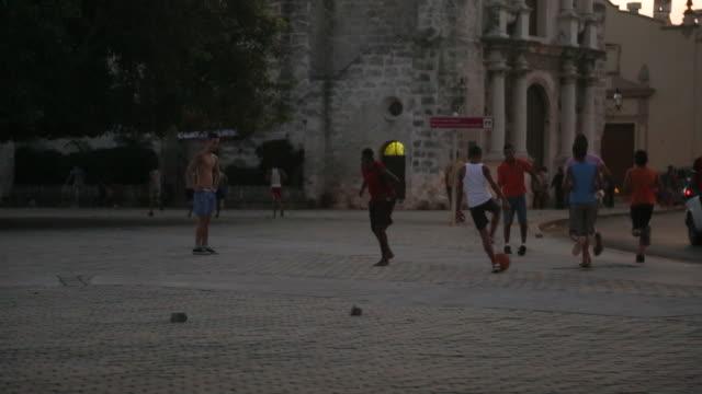 LS of Cuban kids / boys playing soccer in street