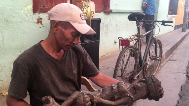 cuban man sculps a piece of wood into a statue on june 20, 2017; in santiago de cuba, cuba. he works on the sidewalk passing right in front of his... - mixed race person stock videos & royalty-free footage