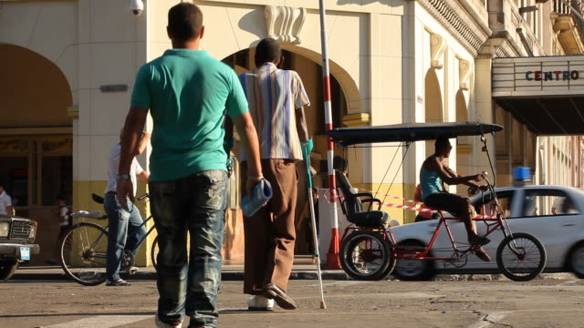 LS of Cuban Man with Crutches & Pedestrians crossing Havana street