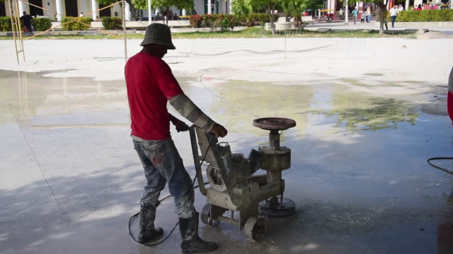 cuban men polishing the floor of the calixto garcia park or plaza / they are using a rustic homemade polishing machine to work the granite floor /... - man and machine stock videos & royalty-free footage