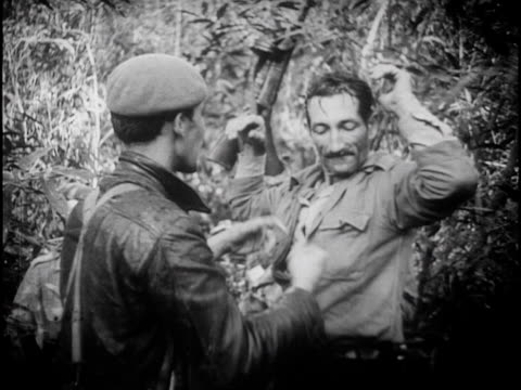 cuban militia marching through jungle searching for enemy soldiers / captured troops marched in front of camera - searching点の映像素材/bロール