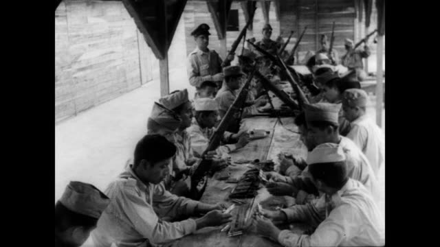 / ls of cuban militia training camp in guatemalan foothills / soldiers sit at long table cleaning guns / men undergo gun training cuban rebels train... - military training stock videos & royalty-free footage