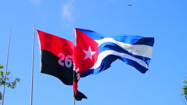 vídeos de stock, filmes e b-roll de cuban national flag and the flag of the july 26th movement waving in santa clara, cuba - número 26
