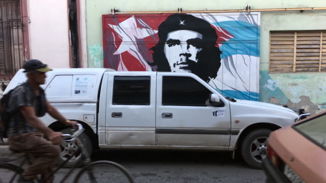 cuban people lifestyle in daytime they are passing in front of an ernesto che guevara poster painting in the tropical city wall - che guevara stock videos & royalty-free footage