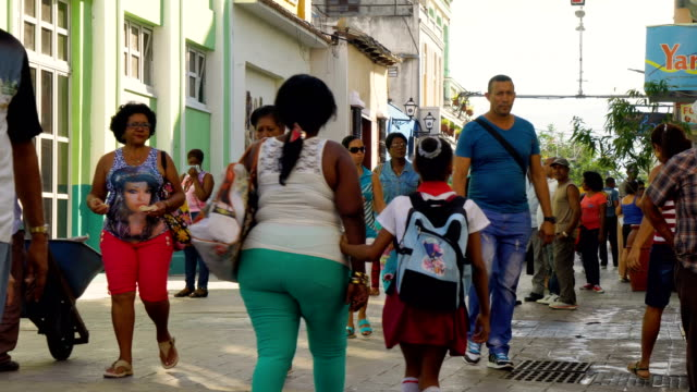 cuban people walking in the city centre of santiago de cuba - cuba video stock e b–roll