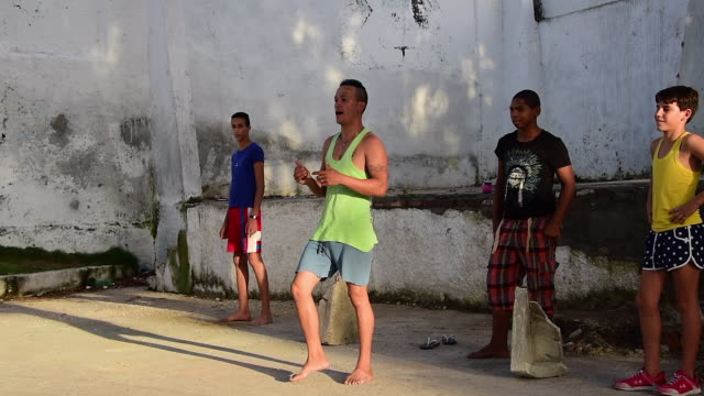 Cuban people youth recreational practice Playing baseball in small urban plaza in an inside neighborhood The game has been adapted to the small area...