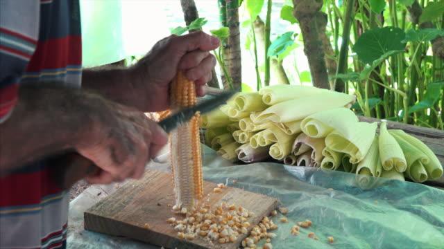 cuban person cutting grains from a corn cob - kuba stock-videos und b-roll-filmmaterial