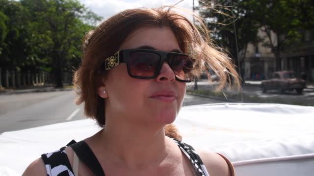 Cuban real people tourist woman sightseeing Havana city in old American convertible car-Havana,Cuba