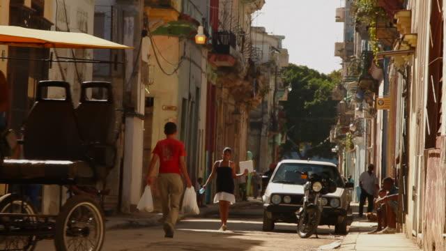 ls, cuban street with cars and pedestrians, havana - ペディキャブ点の映像素材/bロール