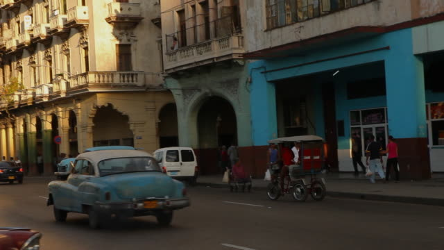 MS of Cuban street with vintage cars & pedestrians