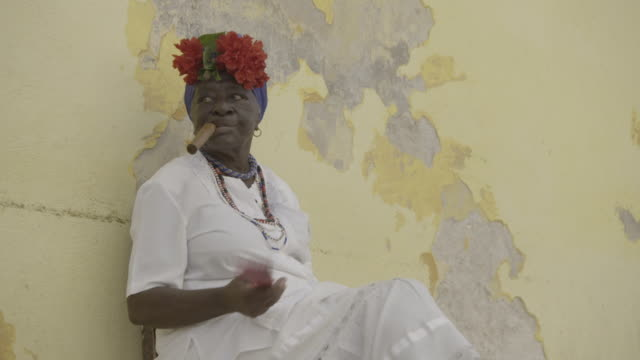 stockvideo's en b-roll-footage met cuban woman smokes cigar and waves fan - cuba