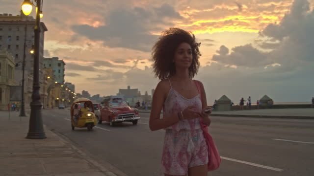 cuban woman walking at the malecon - cuba video stock e b–roll