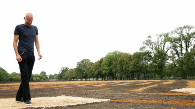 cubanamerican artist jorge rodriguezgerada walks through and talks about his sixacre sand and soil 'facescape' on the jfk hockey field along the... - field hockey stock videos and b-roll footage