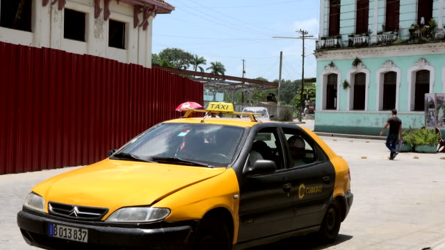 vidéos et rushes de a cubataxi and a horsedrawn carriage pass in front of the colonial building that is being revitalized after raul castro took power many old buildings... - révolution cubaine