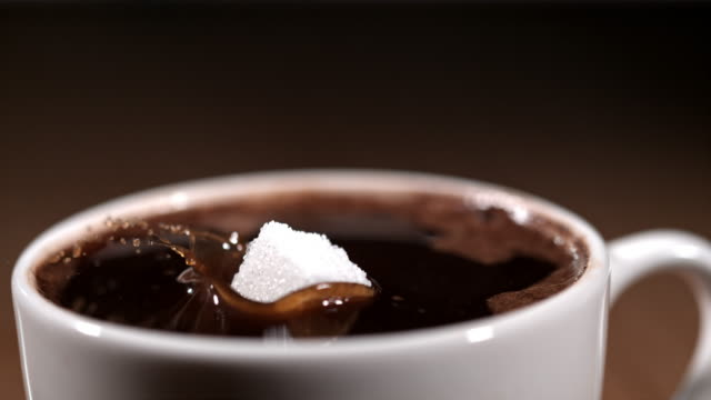SLO MO Cube of sugar falling into a cup of coffee