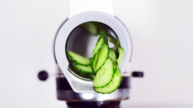 gurken werden in scheiben geschnitten in einer küchenmaschine - hergestellter gegenstand stock-videos und b-roll-filmmaterial