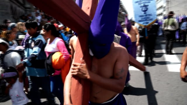 cucurucho carries wooden cross while holly friday procession - poder点の映像素材/bロール