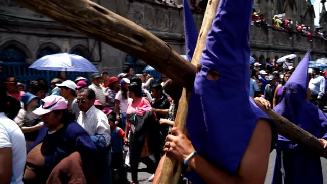 cucurucho carries wooden cross while procession of holly friday - poder点の映像素材/bロール
