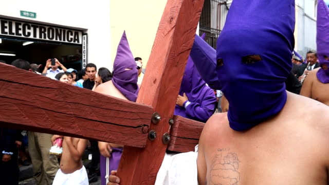 cucurucho holds wooden cross while procession of holly friday - poder点の映像素材/bロール