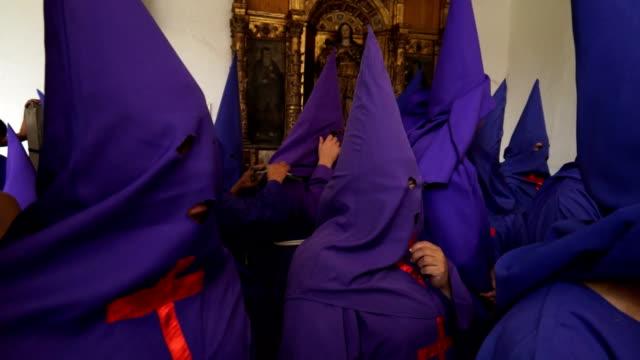 cucuruchos get ready to enter procession walking along church paths - poder点の映像素材/bロール