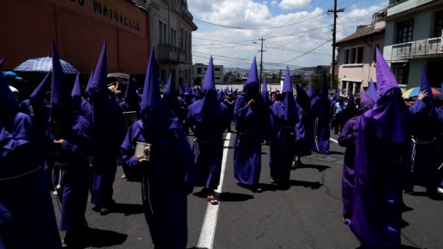 cucuruchos walk along quito streets as part of the holly friday procession - poder点の映像素材/bロール