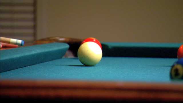 mcu cue stick taking aim hitting white cue ball tracking solid 1 yellow ball rolling across pool table to a stop unidentifiable male sitting bg cue... - cue ball stock videos & royalty-free footage