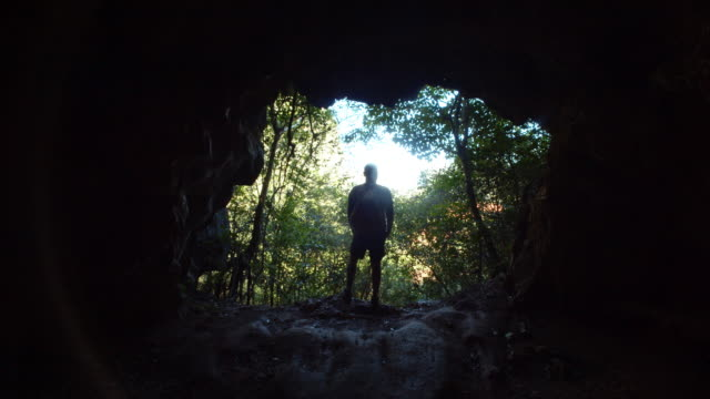 cueva de la vaca, viñales, cuba. man walking out from a cave - standing out from the crowd stock videos & royalty-free footage
