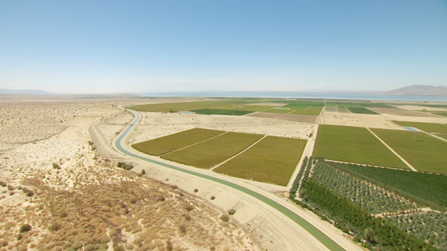 ws aerial pov cultivated farmland and aqueduct in desert valley with the salton sea bordered by mountains in the distance / california, united states - aqueduct stock videos and b-roll footage