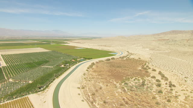ws aerial pov cultivated farmland in desert valley bordered by aqueduct and sandy rocky foothills with mountains in distance / california, united states - foothills stock videos & royalty-free footage