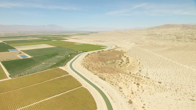 ws aerial pov cultivated farmland in desert valley bordered by aqueduct and sandy rocky foothills with mountains in distance / california, united states - crop stock videos and b-roll footage