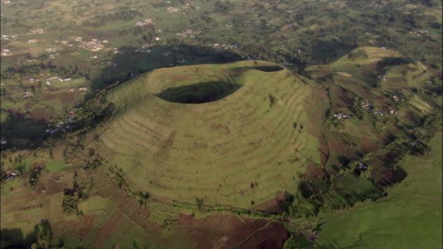vidéos et rushes de aerial, cultivated volcano surrounded with villages, bwindi impenetrable national park, uganda - patchwork landscape