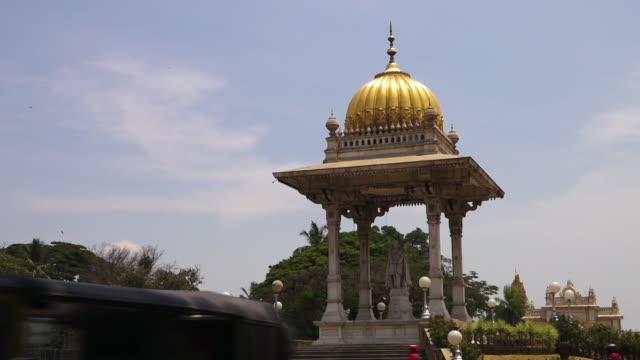 A cultural statue in India stands below a dome